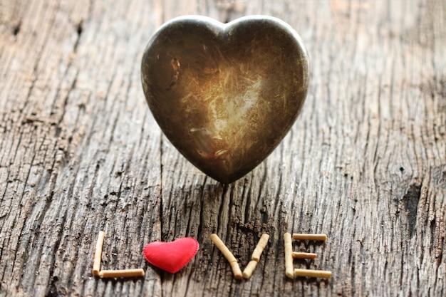 Słowo miłość z czerwonym i metalowym sercem w kształcie walentynki