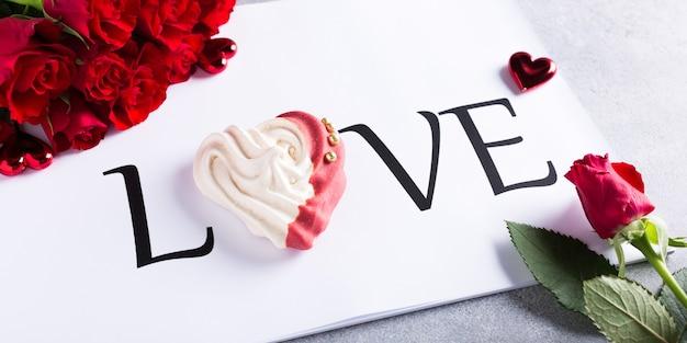 Słowo miłość z domową bezą w kształcie serca z czerwonymi różami. koncepcja walentynki, kopia przestrzeń