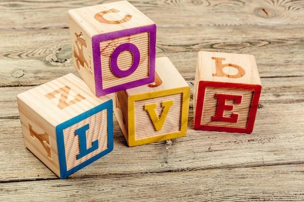 Słowo miłość z drewnianych klocków dla dzieci na drewnianym stole