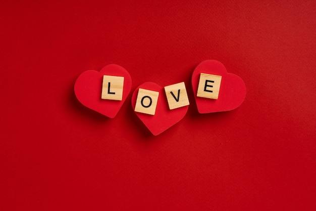 Słowo miłość z drewnianych klocków leży na sercach na czerwonym tle