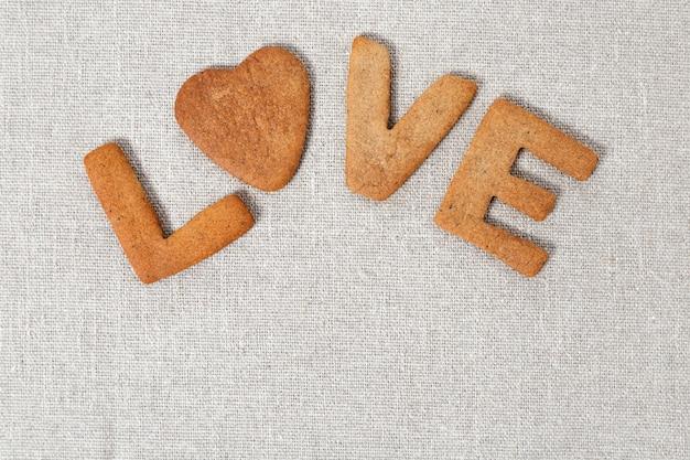 Słowo miłość z herbatników z imbirem na worze lub szorstkiej szmatce