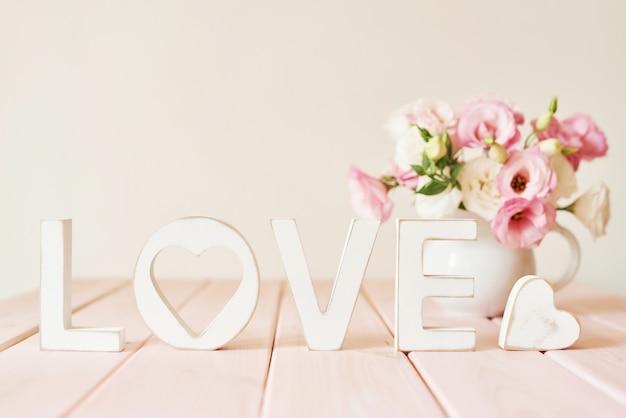 Słowo miłość z kwiatami na stole