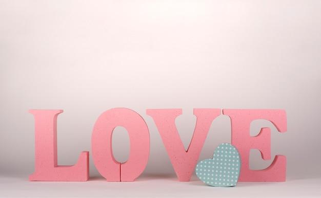 Słowo miłość z różowymi literami z korka i małym tekturowym pudełkiem w kształcie serca. koncepcja walentynki