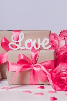Słowo miłość zapisane białymi literami na pudełkach z różowymi wstążkami