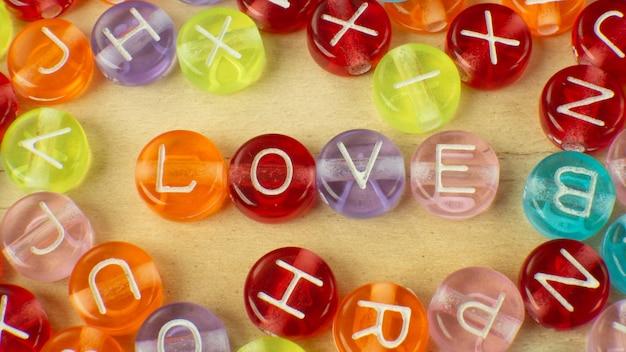 Słowo miłości na wielokolorowych koralikach alfabetu dla zawartości tła