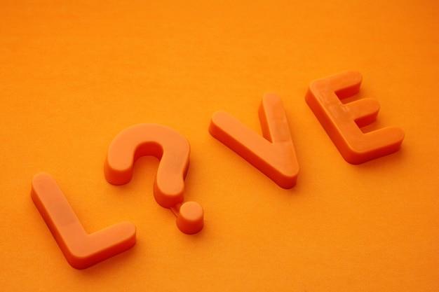 Słowo miłosne to litera wykrzyknika, ułożona pomarańczowymi literami na pomarańczowym tle