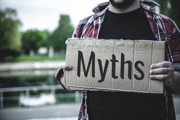 Słowo mity na rozdartym papierze. koncepcja mitów.