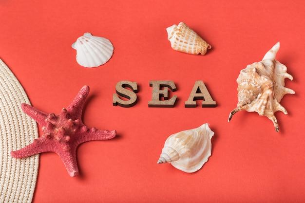 Słowo morze z drewnianych liter. muszle, rozgwiazdy i część kapelusza. żywe tło koralowe. koncepcja morska