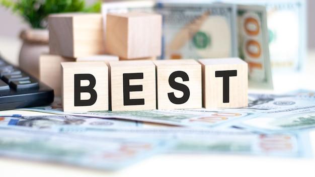 Słowo najlepsze na drewnianych kostkach, banknotach i kalkulatorze na tle koncepcji biznesowej i finansowej