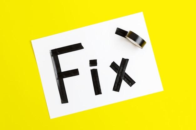 Słowo naprawić taśmy elektrycznej na białym papierze, żółte tło.