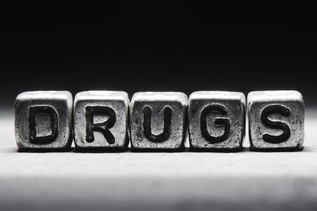 Słowo narkotyki na metalowych kostkach na czarnym tle