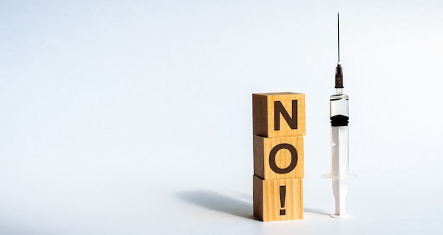 Słowo nie jest zapisane na drewnianych kostkach leżących na stole obok przezroczystej medycznej strzykawki. białe tło. pojęcie.