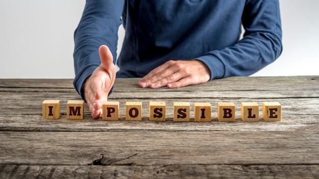 Słowo niemożliwe - możliwe na blokach oddzielonych ręką mężczyzny na rustykalnym starym drewnianym biurku.