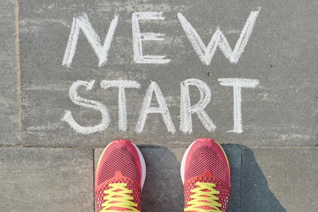 Słowo nowy początek napisane na szarym chodniku z nogami kobiety