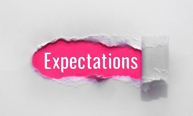 Słowo oczekiwania napis na niebieskim papierze rozdartym.