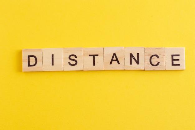 Słowo odległość wykonane z drewnianych liter na żółtym tle.