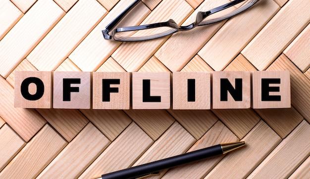 Słowo offline jest napisane na drewnianych kostkach na drewnianej powierzchni obok długopisu i okularów.