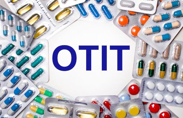 Słowo otit jest napisane na jasnym tle otoczonym wielokolorowymi opakowaniami z tabletkami. koncepcja medyczna