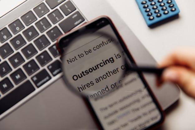 Słowo outsourcingu na ekranie telefonu i szkle powiększającym
