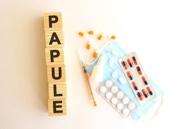 Słowo papuła składa się z drewnianych kostek na białej powierzchni z lekarstwami i maską medyczną.