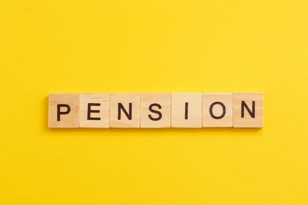 Słowo pension wykonane z drewnianych liter na żółtym tle.