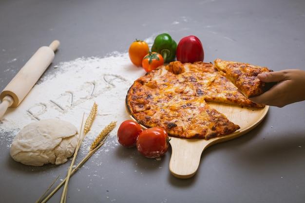Słowo pizza napisana na mące z pyszną pizzą