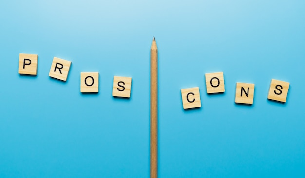 """Słowo """"plusy i minusy"""" w drewnianym bloku na niebieskiej powierzchni oddzielone ołówkiem"""