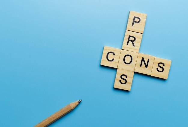 """Słowo """"plusy i minusy"""" w drewnianym bloku na niebieskiej powierzchni ołówkiem"""