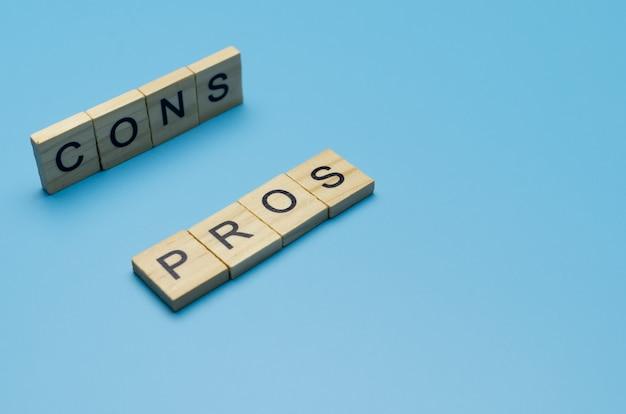 """Słowo """"plusy i minusy"""" w drewnianym bloku na niebieskiej powierzchni wskazanej ołówkiem"""