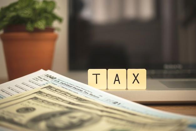 Słowo podatku na drewnianych klockach i formularz wniosku 1040 na komputerze stacjonarnym z laptopem i rachunkami dolarowymi. zdjęcie koncepcji opodatkowania