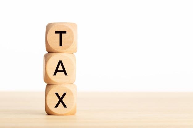 Słowo podatku w drewnianych klockach na stole. pojęcie opodatkowania.