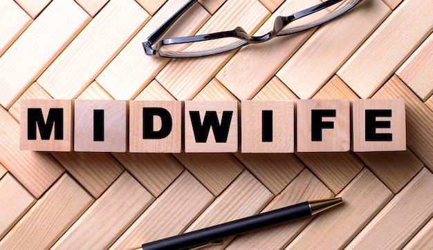 Słowo położna jest zapisane na drewnianych kostkach na drewnianym tle obok długopisu i okularów