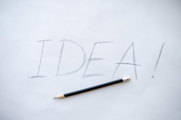 Słowo pomysł. kreatywna koncepcja. drewniane litery słowa idea z ręcznie pisanym akronimem, zdjęciem ołówkiem na białym papierze i interaktywnym