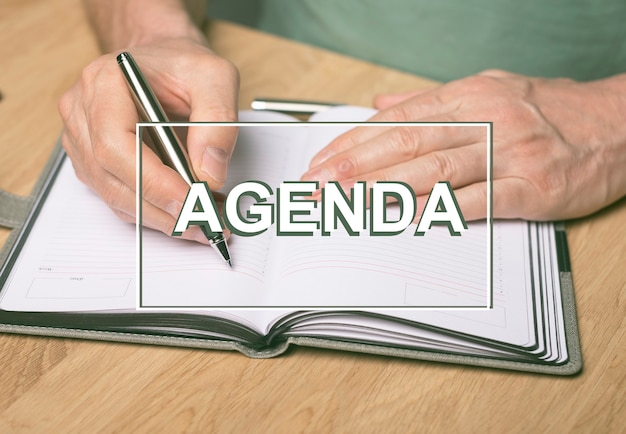 Słowo porządku obrad. napis na zdjęciu rąk piszących w terminarzu lub organizerze.