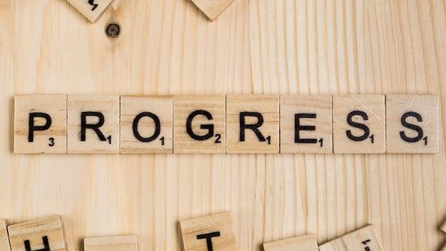Słowo postępu na drewnianych płytkach