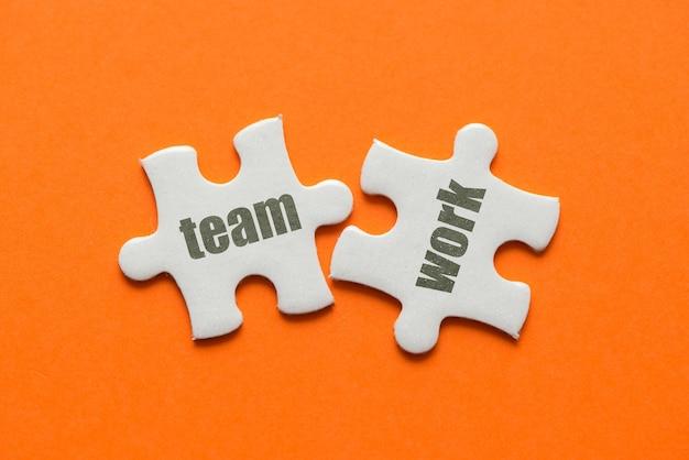 Słowo praca zespołowa na dwóch pasujących układankach na pomarańczowo.