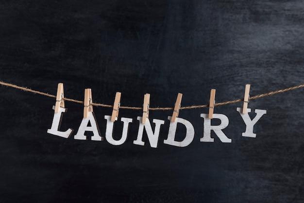 Słowo pranie jest zawieszone na spinaczach do bielizny. czyszczenie na sucho. koncepcja usługi sprzątania.