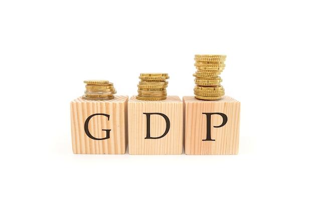 Słowo produkt krajowy brutto pkb na drewnianych klockach i stosach monet