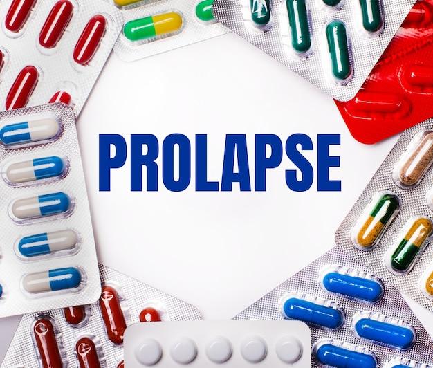 Słowo prolapse jest napisane na jasnym tle otoczonym wielokolorowymi opakowaniami z tabletkami. koncepcja medyczna