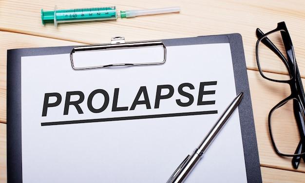 Słowo prolapse jest zapisane na białej kartce papieru obok okularów w czarnych oprawkach, długopisu i strzykawki