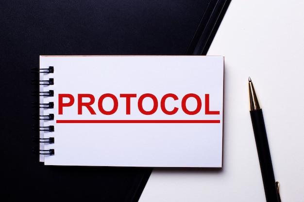 Słowo protokół zapisane na czerwono na czarno-białej ścianie obok długopisu