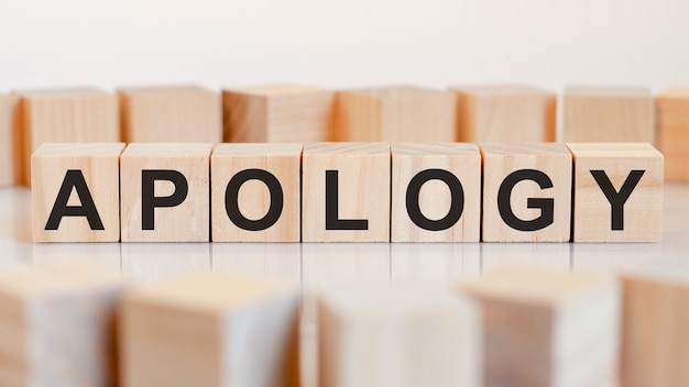 Słowo przeprosiny jest zapisane na drewnianej konstrukcji z kostek. koncepcja biznesowa i finansowa.