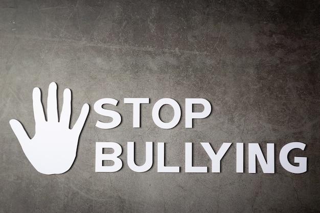 """Słowo """"przestań zastraszać"""" ze znakiem ręki na ciemnej ścianie"""