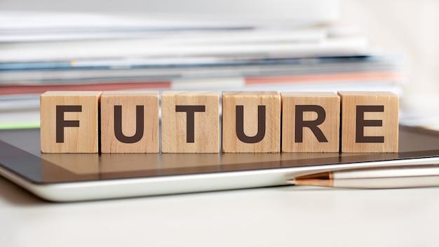 Słowo przyszłość zapisane jest na drewnianych kostkach stojących na notesie. może służyć do biznesu, edukacji, koncepcji finansowej.