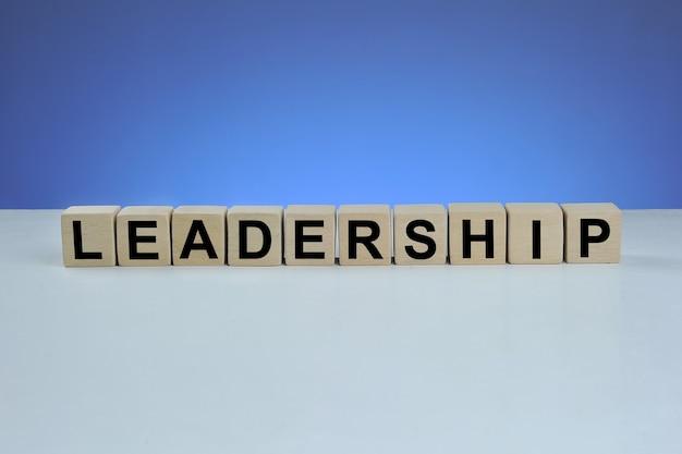 Słowo przywództwa napisane na drewnianej kostce na niebieskim tle