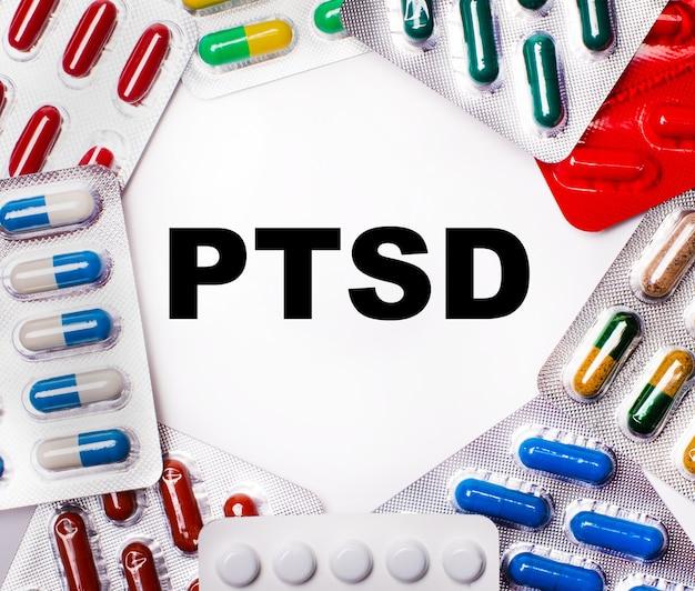 Słowo ptsd pisane na jasnym tle otoczonym wielobarwnymi opakowaniami z tabletkami