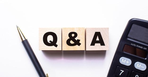 Słowo q and a pytania i odpowiedzi jest zapisane na drewnianych kostkach między długopisem a kalkulatorem na jasnym tle.