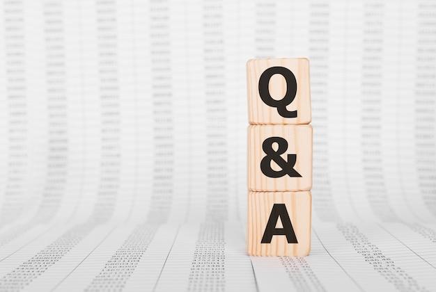 Słowo q and a wykonane z drewnianych klocków, koncepcja biznesowa.