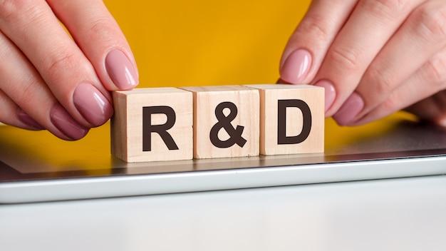 Słowo r i d napisane jest na drewnianych kostkach stojących na zeszycie. selektywne skupienie. biznes, edukacja, koncepcja finansowa. r i d - skrót od badań i rozwoju