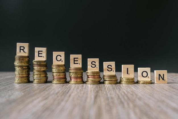 """Słowo """"recesja"""" na malejących monetach."""